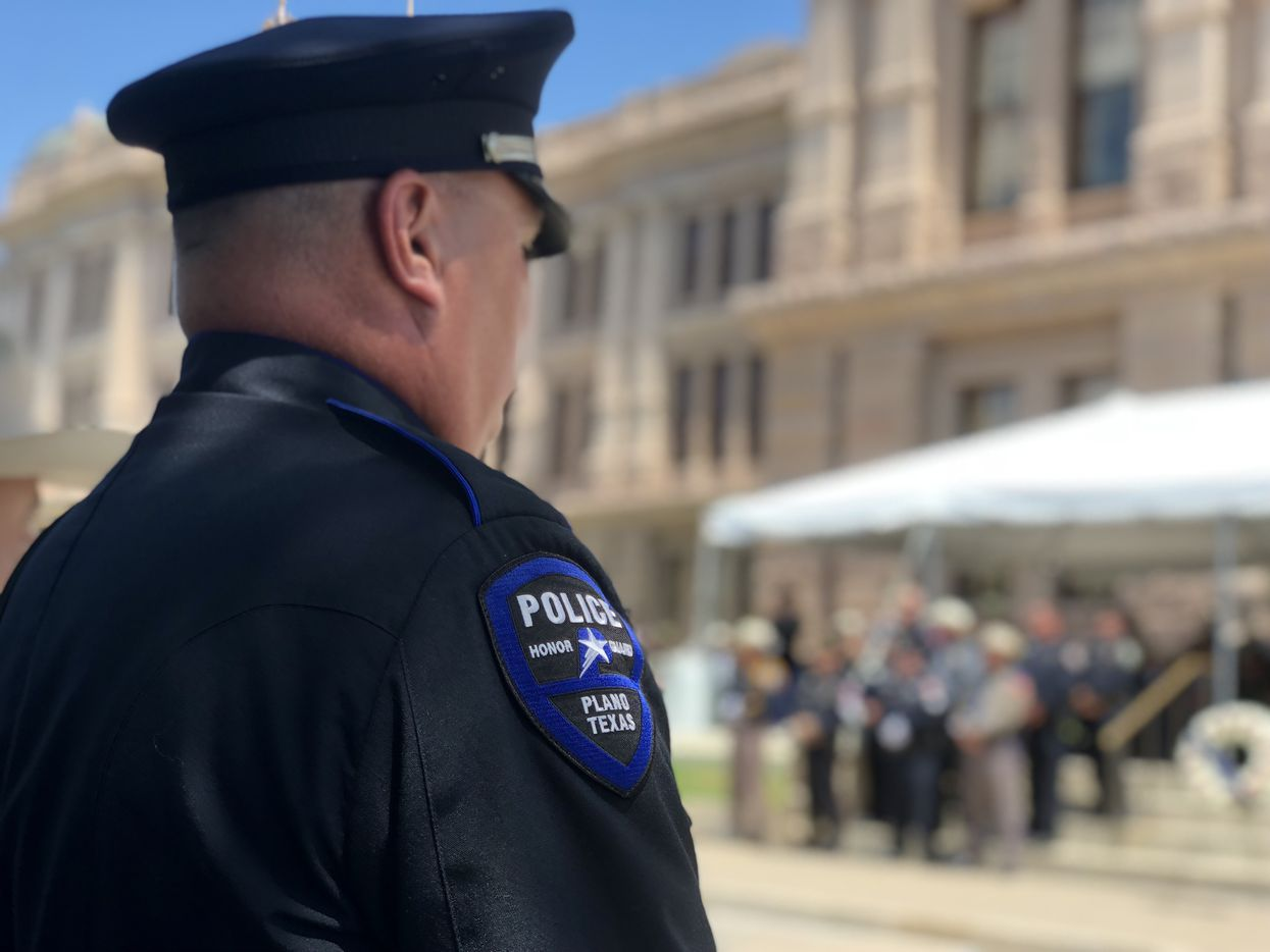 A member of the honor guard watches the Texas Peace Officers' Memorial ceremony from under a tree on Monday, May 7, 2018, in Austin, Texas.