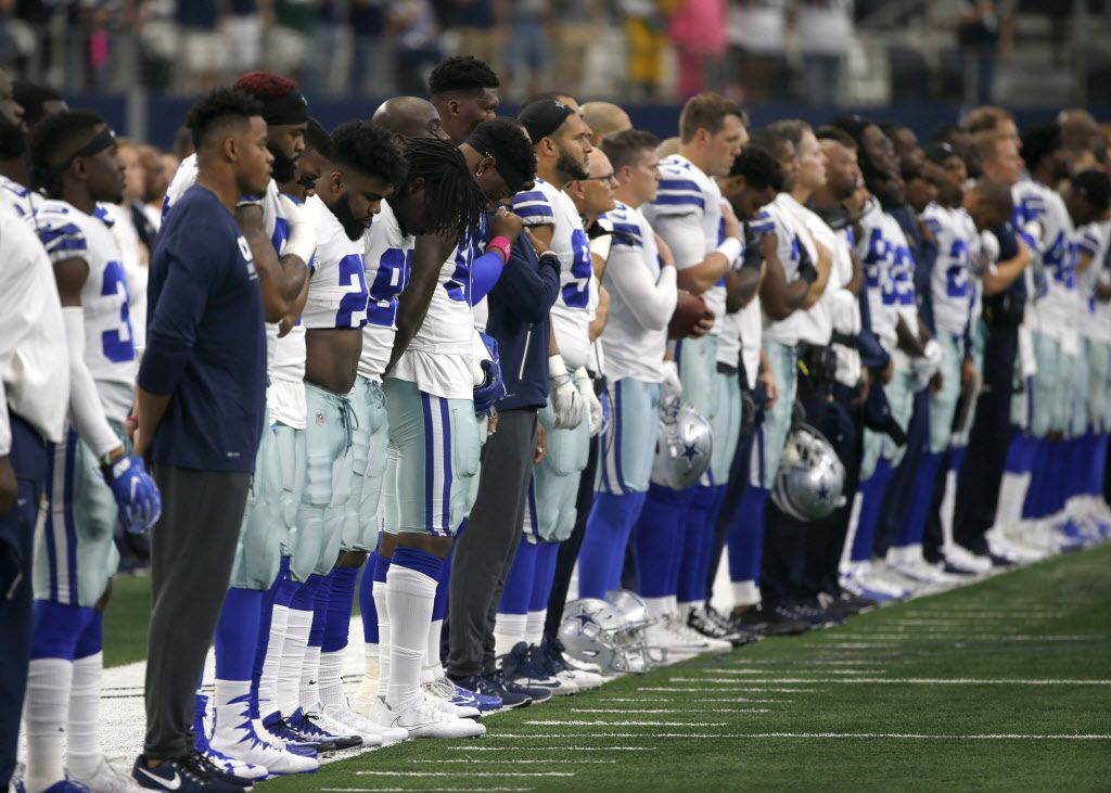The Dallas Cowboys and staff stand on the sideline during the playing of the national anthem before the first half of an NFL football game against the Green Bay Packers on Sunday, Oct. 8, 2017, in Arlington, Texas. (AP Photo/Ron Jenkins)