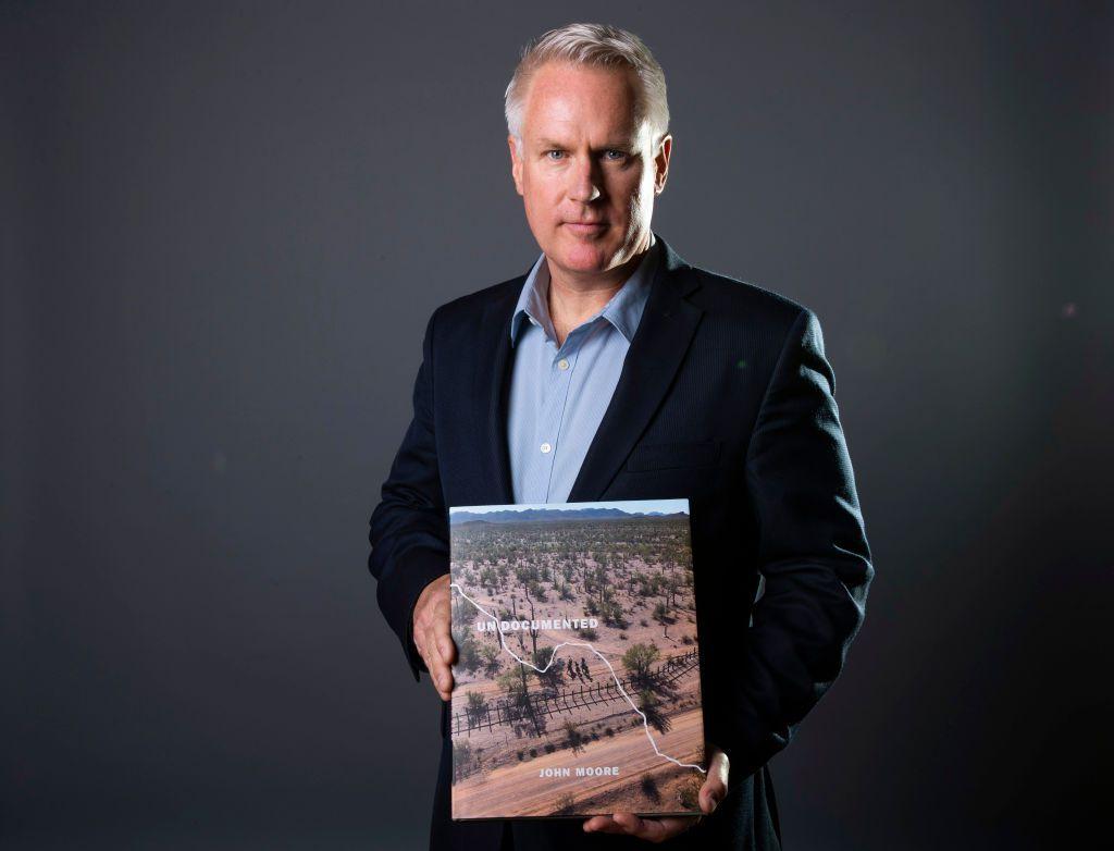 """El fotógrafo John Moore posa con su libro """"Undocumented:(Indocumentados) durante el lanzamiento el 19 de abril de 2018 en Ciudad de México. Foto: Hector Vivas / Getty Images"""