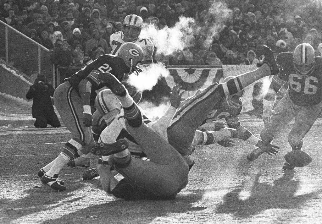 """Players spill in all directions as a fumble occurs in the third period of the National Football League Championship game, known as """"The Ice Bowl"""" between the Dallas Cowboys and the Green Bay Packers at Lambeau Field, in Green Bay, Wisc. Dallas quarterback Don Meredith (white jersey, #17) fumbles and Herb Adderly of the Packers (#26, partially hidden) reaches to recover it in the game played in sub-zero temperatures. (AP Photo/File)"""