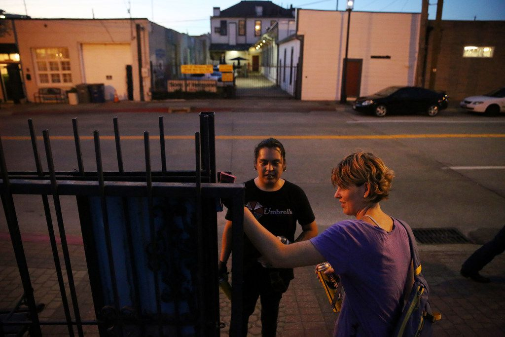 Angel Pacheco (center) and Adrienne Lichliter attempt to clean up a gate as community activists remove graffiti. Pacheco is a longtime regular in Deep Ellum and says that the community has become home to him.