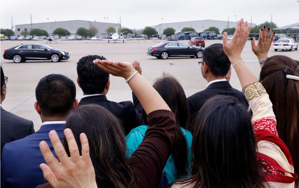 Attendants wave as the Aga Khan leaves in his motorcade.