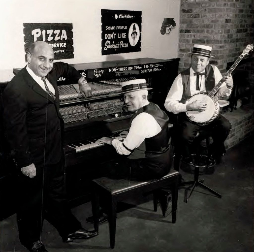 Andy Stasio (left), who opened the first Shakey's Pizza Parlor in DFW in the 1960s, posed inside the Northwest Highway restaurant with banjo and piano players. The photo, taken around 1965, was provided by his son.