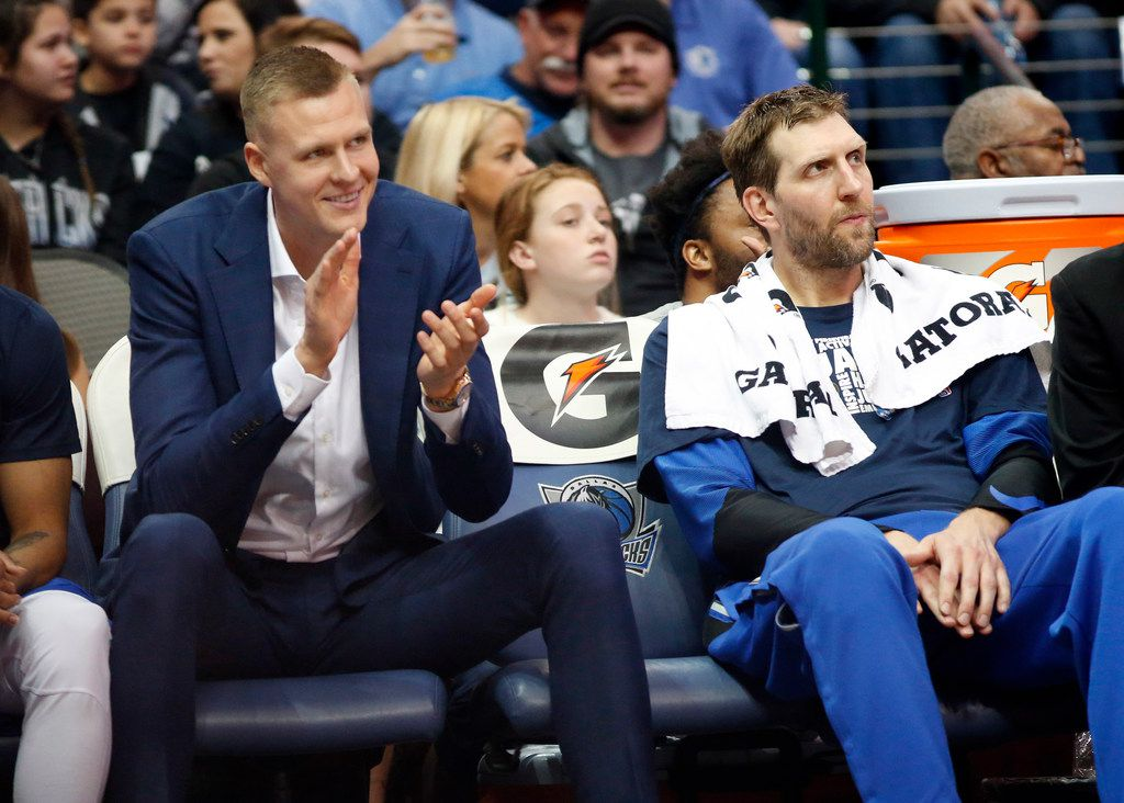 Dallas Mavericks forward Kristaps Porzingis (left) applauds his teammates alongside Dallas Mavericks forward Dirk Nowitzki (right) during the fourth quarter against the Denver Nuggets at the American Airlines Center in Dallas, Friday, February 22, 2019. The Mavericks lost, 114-104. (Tom Fox/The Dallas Morning News)