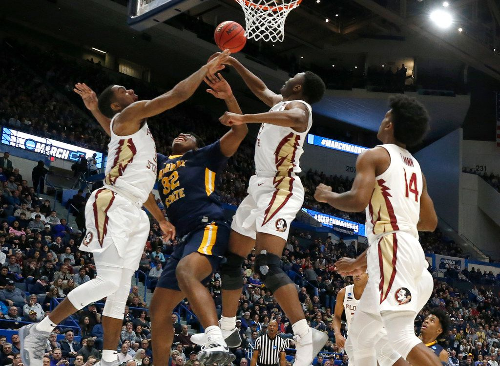 Murray State's Darnell Cowart (32) has his shot blocked by Florida State's Trent Forrest, left, and Florida State's Mfiondu Kabengele, right, as Terance Mann (14) looks on during the first half of a second round men's college basketball game in the NCAA Tournament, Saturday, March 23, 2019, in Hartford, Conn. (AP Photo/Elise Amendola)
