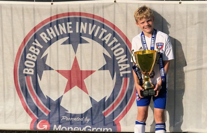 Jake Rhine, son of FC Dallas legend Bobby Rhine, holding the championship trophy for his age bracket at the Bobby Rhine Invitational