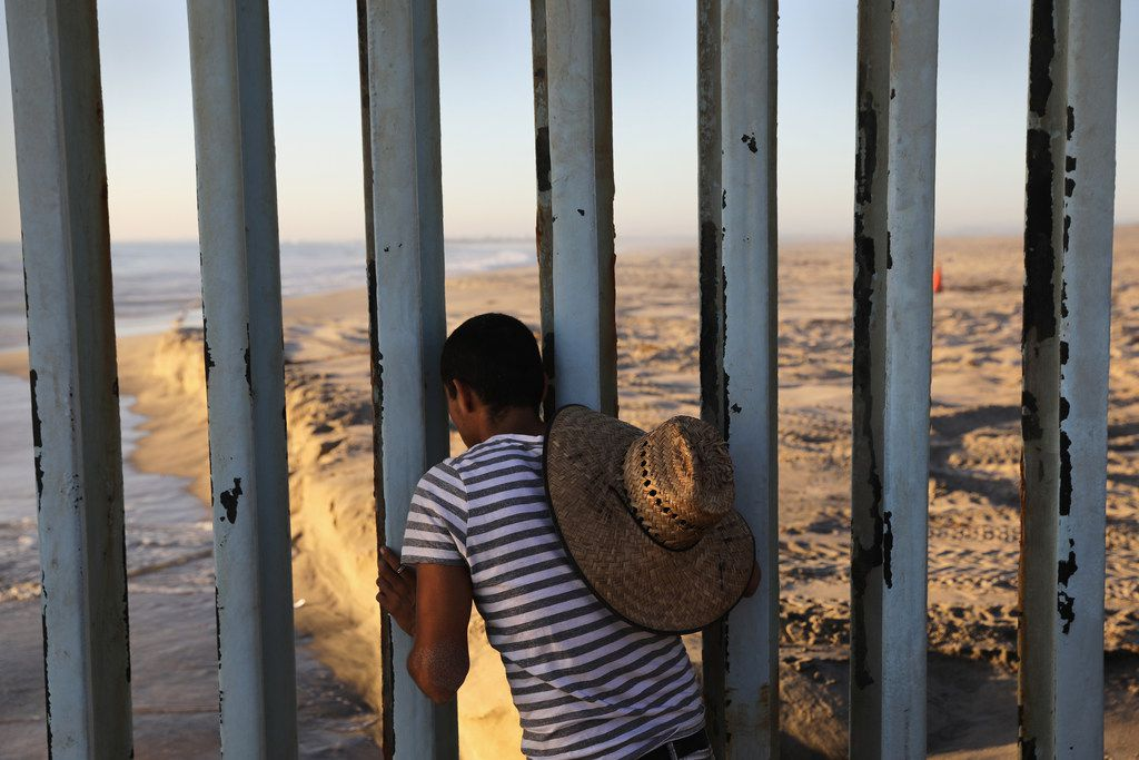 A man looks through the U.S.-Mexico border fence into the United States on September 25, 2016 in Tijuana, Mexico. Friendship Park on the border is one of the few places on the 2,000-mile border where separated families are allowed to meet.  The image appears in Undocumented: Immigration and the Militarization of the United States-Mexico Border.