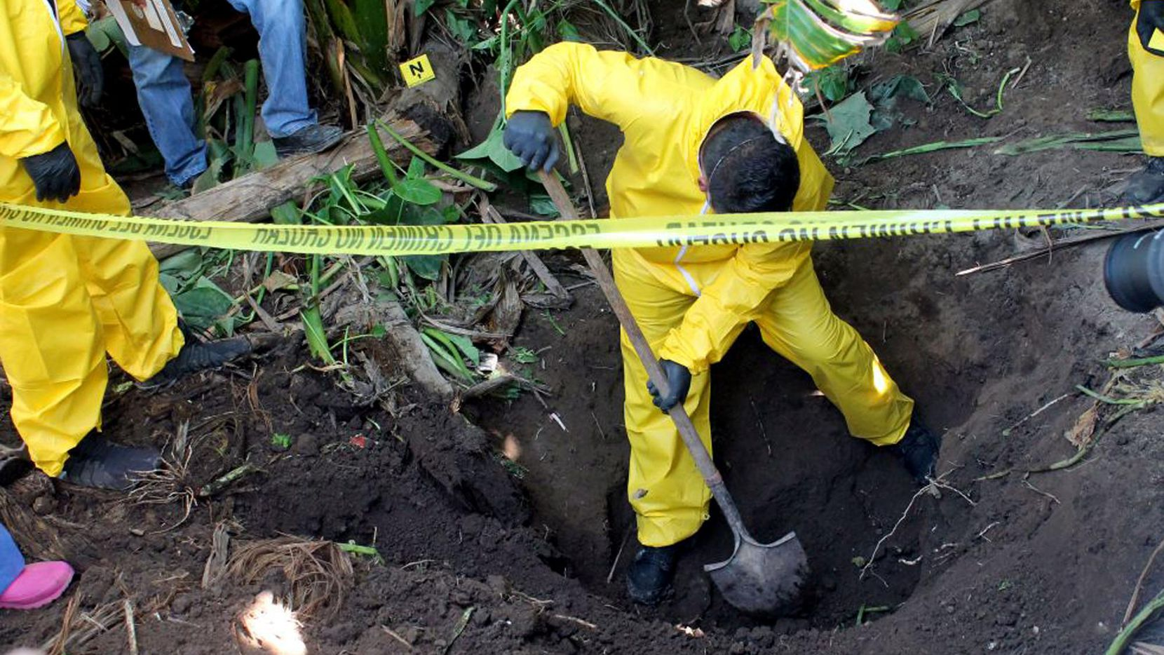 Fotografía distribuída por la In this Jan. 15, 2018 photo, released by the General Prosecutor of Nayarit, a man digs up a clandestine grave in Xalisco, Nayarit state, Mexico. Sniffer dogs led authorities to the grisly discovery of three clandestine graves containing at least 33 bodies in a sugarcane field. Some of the bodies may have been hacked up before being tossed into the pits, and authorities believe they were probably involved in the drug trade. (General Prosecutor of Nayarit via AP) (AP/General Prosecutor of Nayarit)