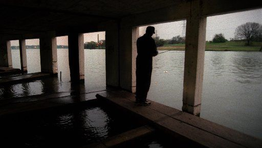 A long-ago photo of a man fishing from the old White Rock Lake boathouse on the T&P Hill..