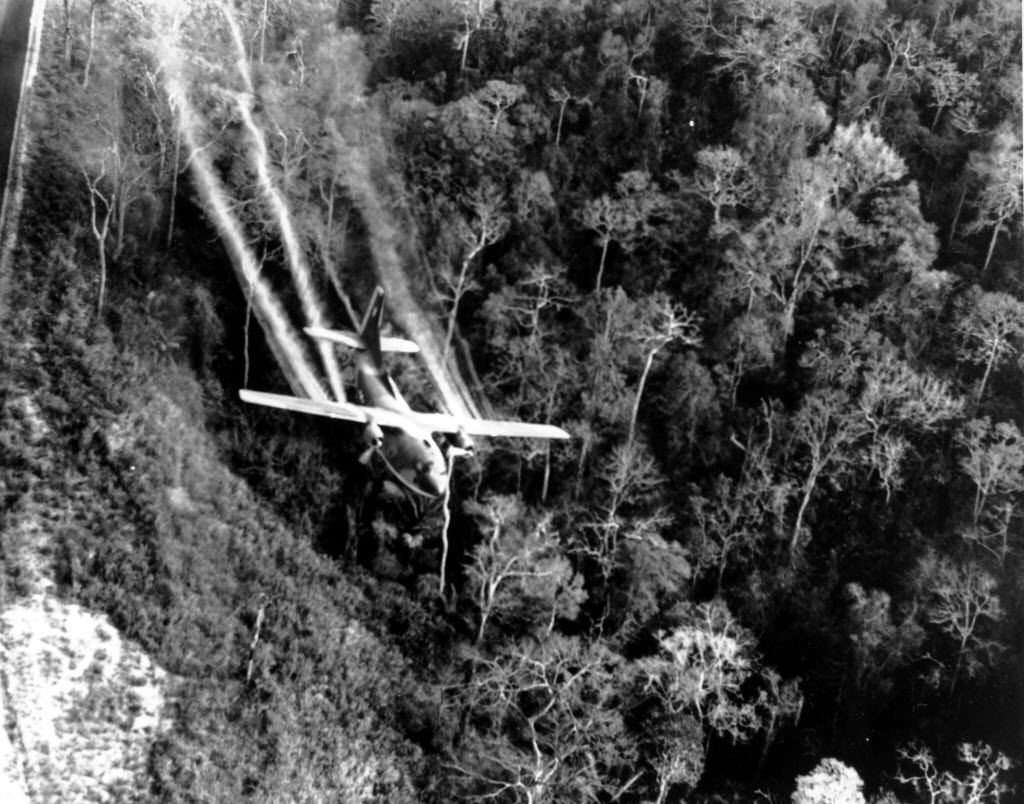 In this May 1966 file photo, a U.S. Air Force C-123 flies low along a South Vietnamese highway spraying defoliants on dense jungle growth beside the road to eliminate ambush sites for the Viet Cong during the Vietnam War. During the war, Air Force C-123 planes sprayed millions of gallons of herbicides over the jungles of Southeast Asia to destroy enemy crops and tree cover.