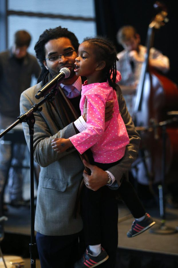 "Professor Darius Ajai Frasure, from Daverse Lounge holds Siedah Yvonne Frasure, 5, as she finishes up the last word of his poem, ""love,"" at the Ideas Stage during The  Dallas Festival of Ideas at  Winspear Opera House in Dallas Feb. 28, 2015. (Nathan Hunsinger/The Dallas Morning News) 03012015xNEWS"