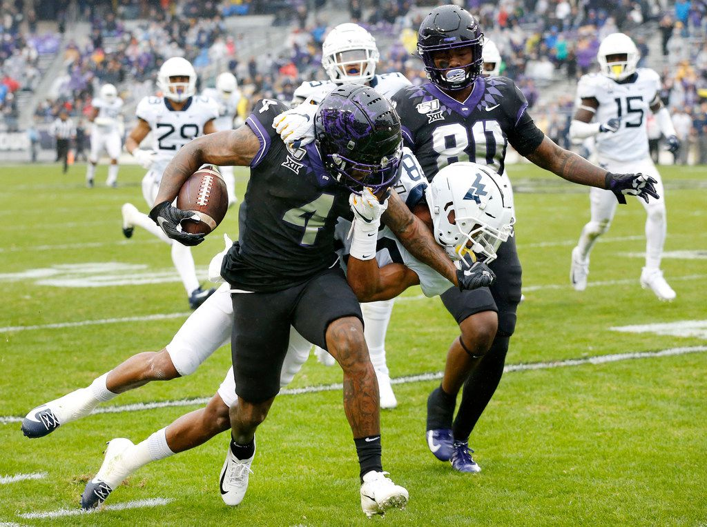TCU Horned Frogs wide receiver Taye Barber (4) stiff arms West Virginia Mountaineers cornerback Keith Washington Jr. (28) as they run down the sideline after a first quarter catch at Amon G. Carter Stadium in Fort Worth, Friday, November 29, 2019.(Tom Fox/The Dallas Morning News)