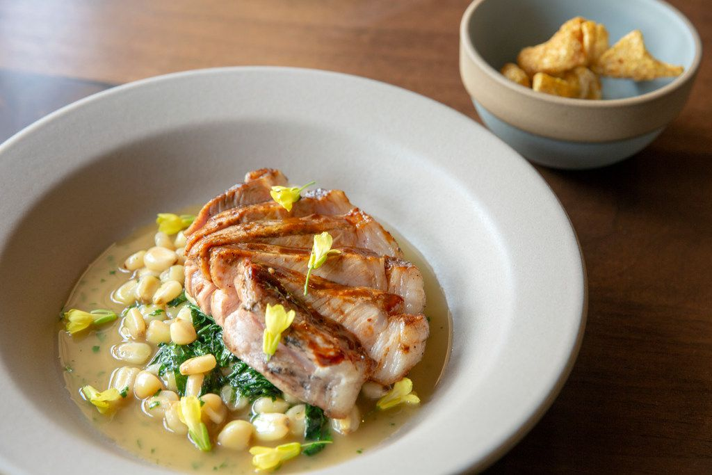 Oak-smoked Hereford pork loin with spigarello, hominy and toasted peanut jus, plus a bowl of crisp chicharrones