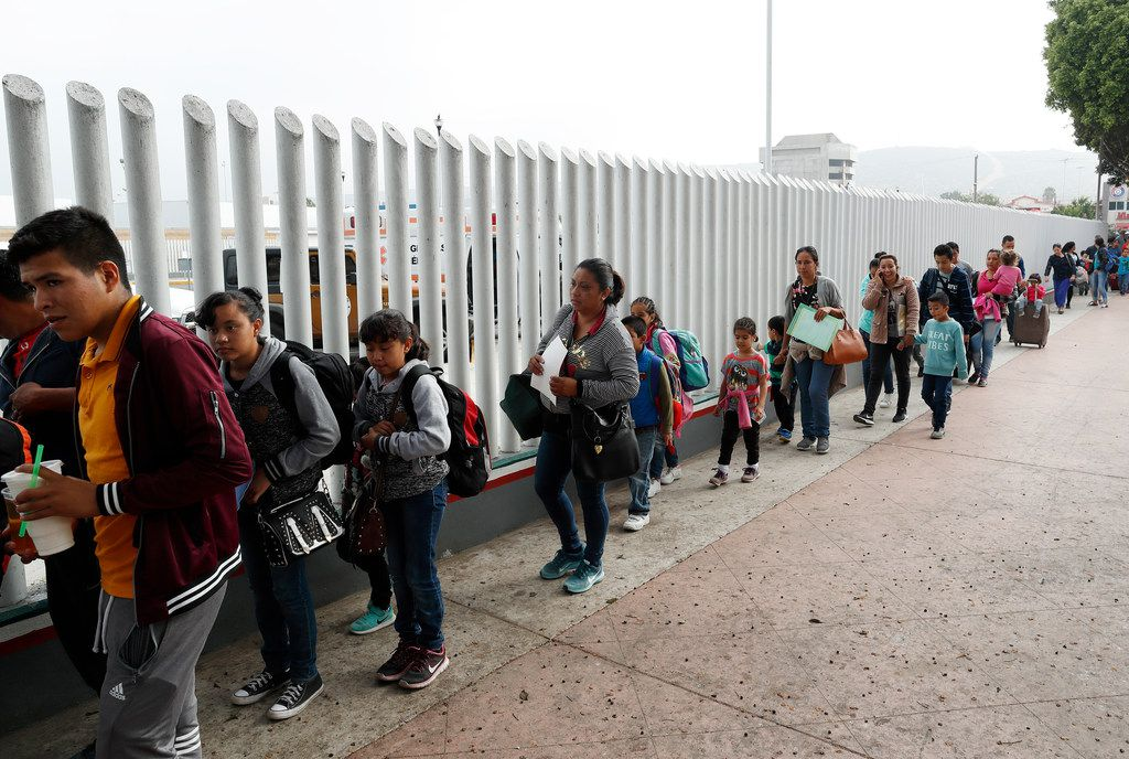 """This July 26, 2018, file photo shows people lining up to cross into the United States to begin the process of applying for asylum near the San Ysidro port of entry in Tijuana, Mexico. Homeland Security's watchdog says immigration officials were not prepared to manage the consequences of its """"zero tolerance"""" policy at the border this summer that resulted in separation of nearly 3,000 children from parents."""