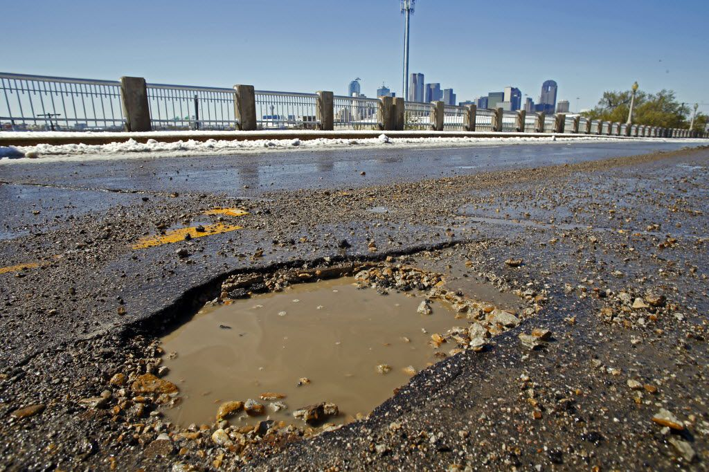 A pothole along Malcolm X Blvd on Thursday, March 5, 2015 in Dallas,Texas. The snow storm delayed and canceled flights, business and  school throughout North Texas. (Nathan Hunsinger/The Dallas Morning News) 04152015xBRIEFING