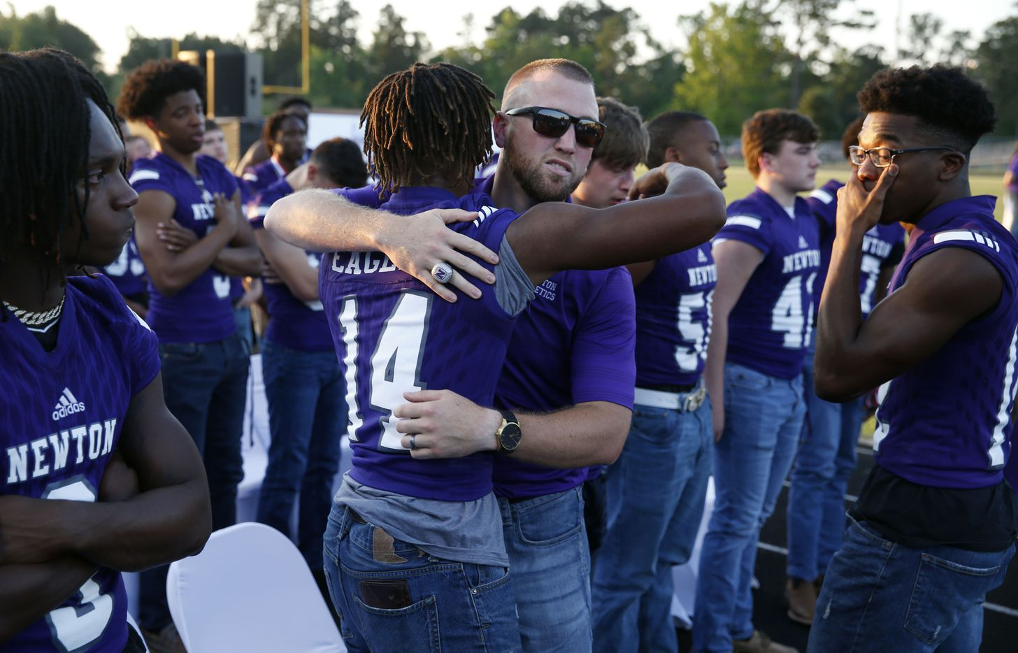 """Newton current head football coach and son Drew Johnston hugs Newton's Dominique Seastrunk (14) during the memorial service for Newton High School head football coach William Theodore """"W.T."""" Johnston at Curtis Barbay Field at Newton High School in Newton, Texas on Wednesday, May 15, 2019. (Vernon Bryant/The Dallas Morning News)"""