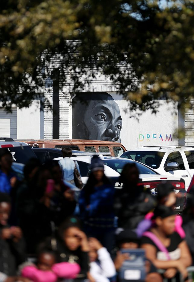 A mural in the likeness of Martin Luther King, Jr. can be seen while people watch the parade.