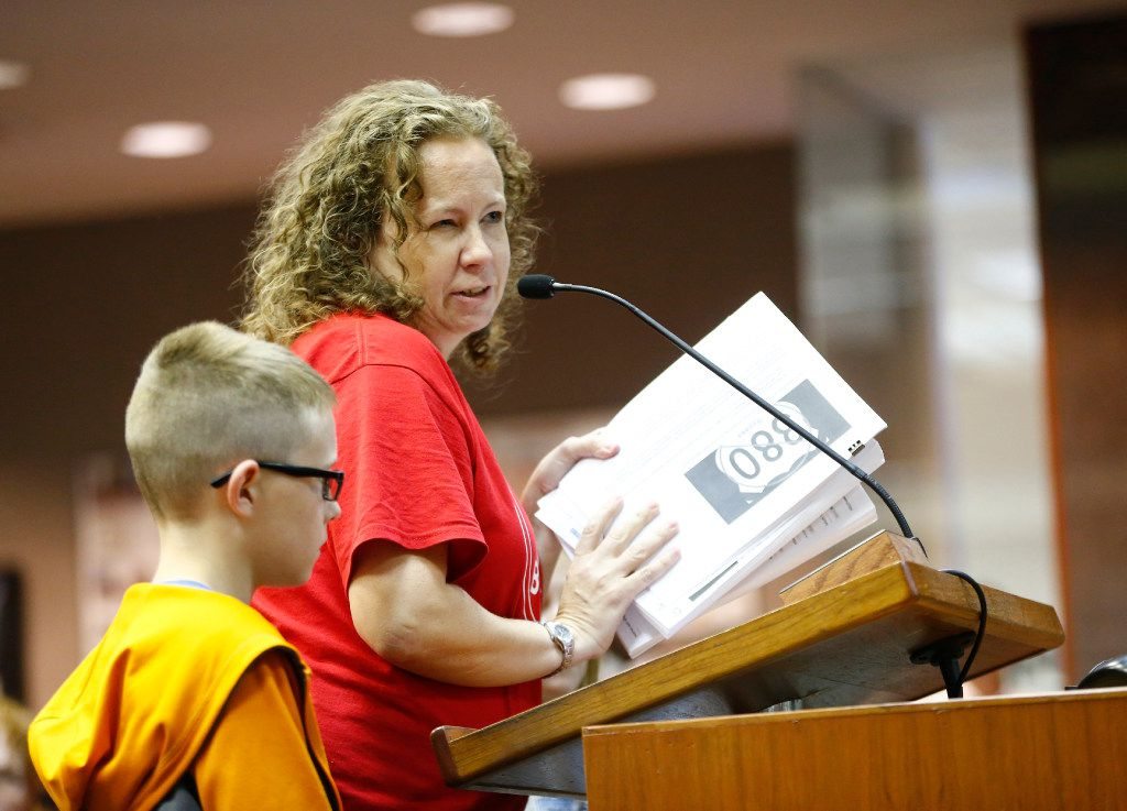 Tracy Thomas (right) with her son Hudson Thomas submits a petition opposed to a U.S. Highway 380 bypass during a McKinney City Council meeting on July 18, 2017.