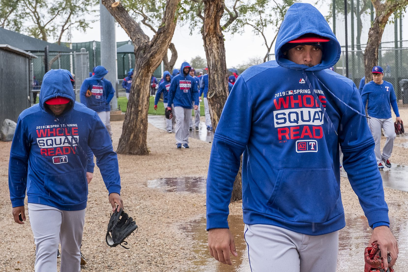 Texas Rangers infielder Ronald Guzman (right) bundles up against a cold rain while walking between practice fields on Feb. 22 at the club's spring training facility in Surprise, Ariz..