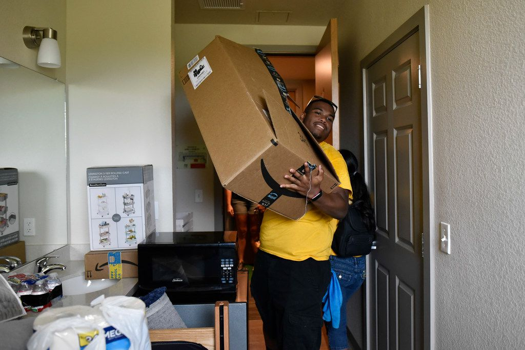 Student volunteer Joseph Lashley (left) carries a cardboard box for an incoming freshman as students moved into the dorm at the University of North Texas at Dallas.