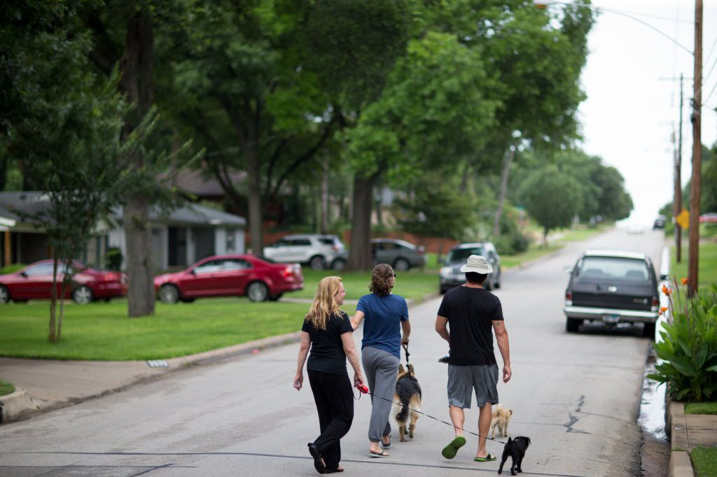 Christina  Martinez (left) walks her dog with her daughter Hana and,  husband Kelly in the Kiestwood neighborhood of Dallas.