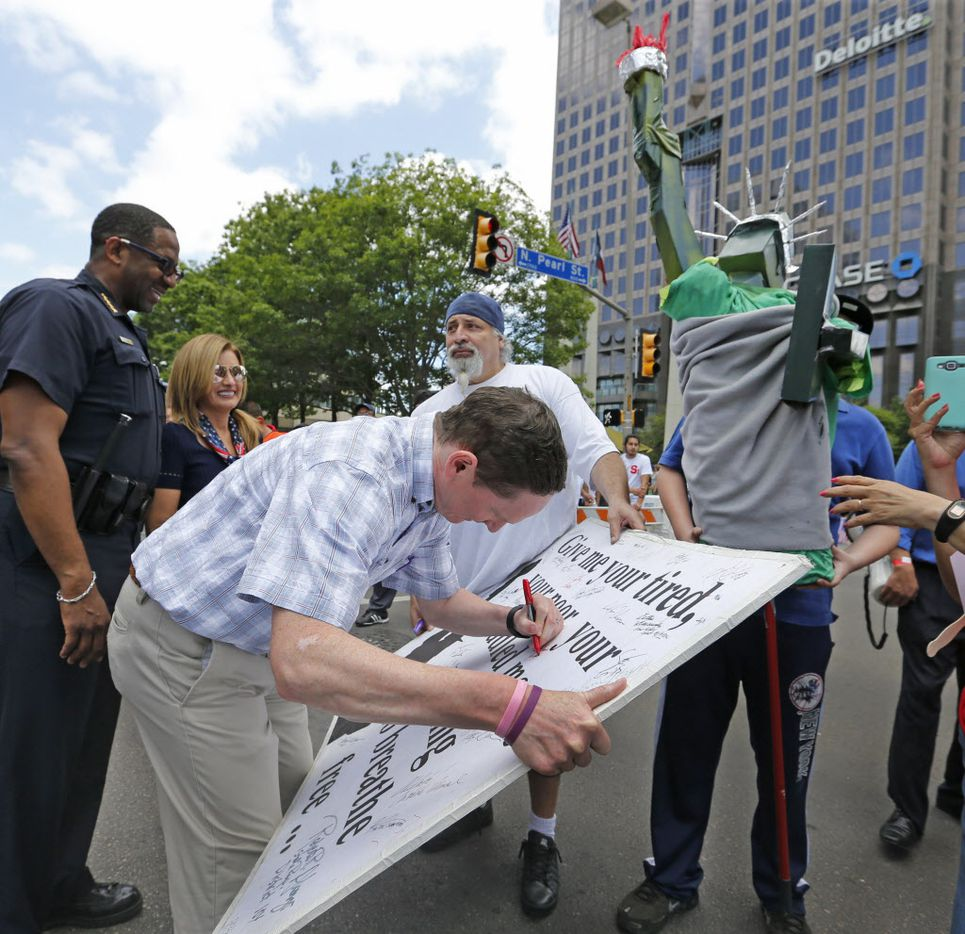 Dallas County Judge Clay Jenkins signs a poster during the Mega March, which started at the Cathedral Shrine of Our Lady Guadalupe in downtown Dallas, photographed on Sunday, April 9, 2017.