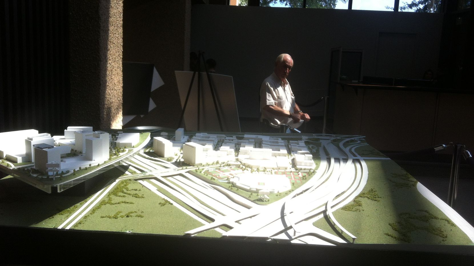 A man slows to look at miniature model of a mini city on the abandoned Texas Stadium site in the Irving City Hall lobby in June 2014. Exclusive negotiations between the city and the development firm that built the model expired last month, the model has been moved from City Hall, and the most ambitious project in Irving sits in limbo.    Photo taken June 2014.