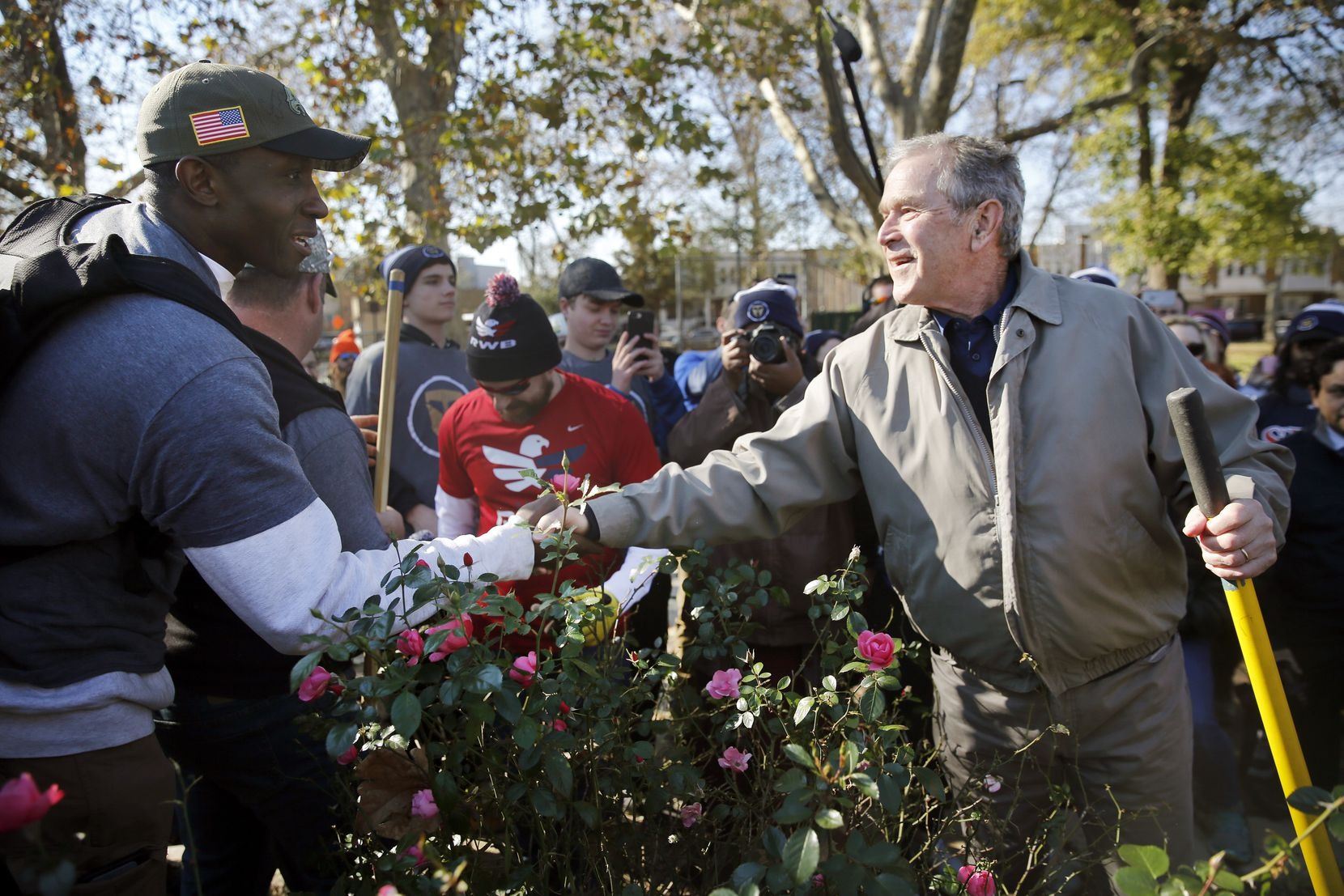 Former President George W. Bush shakes hands and thanks veteran Navy submarine officer Joshua Stewart, who was planting dogwood trees during a Veterans Day landscaping project Sunday in Philadelphia's Point Breeze neighborhood.  Stewart is part of a group of veterans who serve as Character Does Matter mentors for the Travis Manion Foundation.