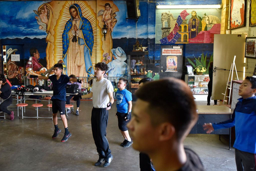 Children of all ages do warm-up exercises before they begin their boxing lesson at Casa Guanajuato in Dallas, Sept. 12, 2019.
