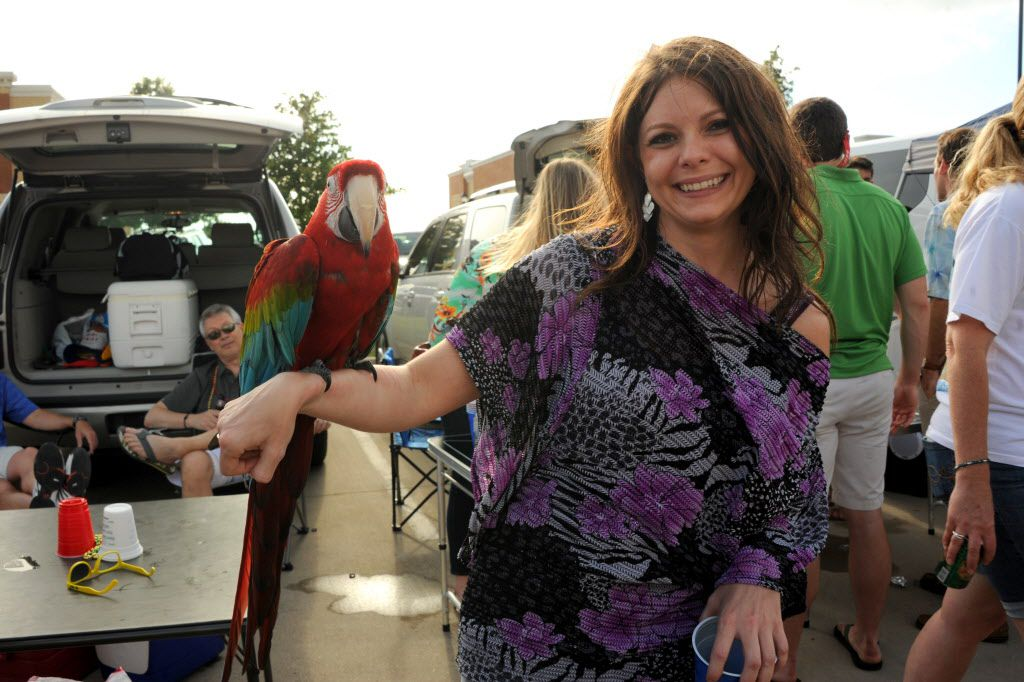 Cassie Hail and Bob the 15-year-old parrot tailgate before the Jimmy Buffett concert at Toyota Stadium in Frisco, TX on May 30, 2015.