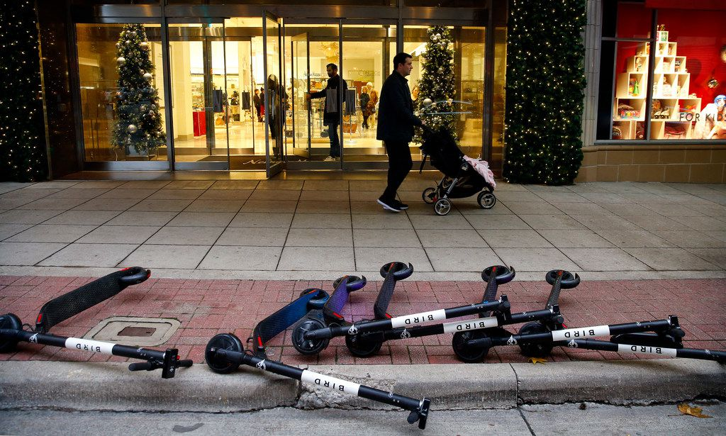 Bird rental scooters lay on the ground outside the Neiman Marcus store in downtown Dallas