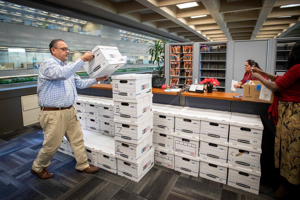 Assistant city secretary Jesus Salazar (left) stacks and counts boxes of petitions after a coalition of labor and faith groups and political activists delivers petitions to at City Hall calling for a city ordinance mandating paid sick time to be placed on the November ballot on Monday, June 11, 2018, in Dallas.