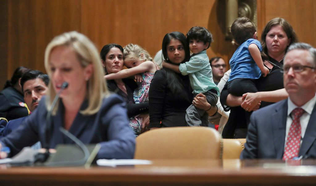 Women carrying children in their arms stand up to protest the opening remarks of Homeland Security Secretary Kirstjen Nielsen (left) during Nielsen's opening remarks before Senate Appropriations subcommittee hearing last month on Capitol Hill.