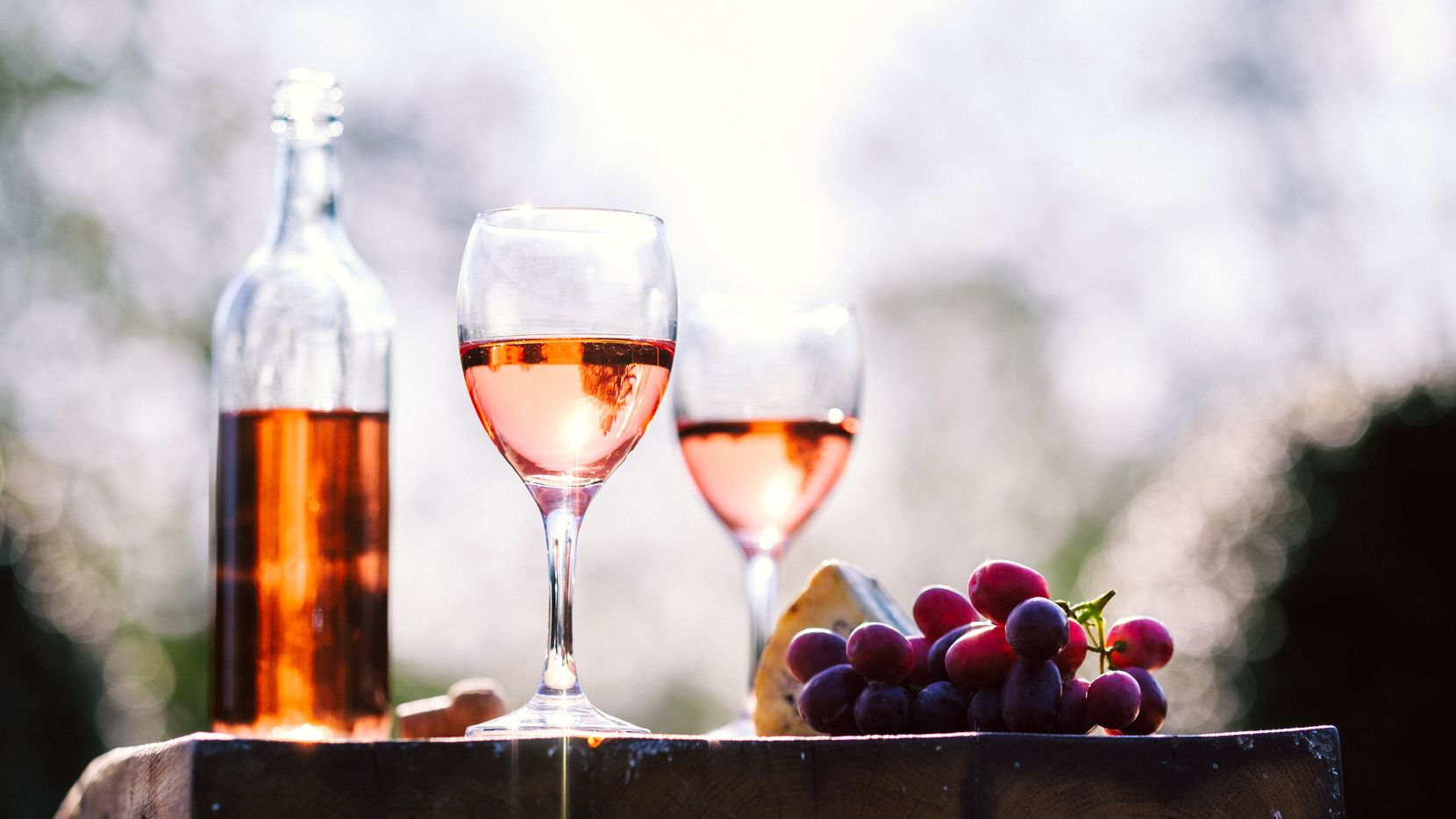 Rose wine filled bottle,glasses and a cork on a large cheese board with red grapes and stilton cheese in a natural sun light environment with a garden background with copy space