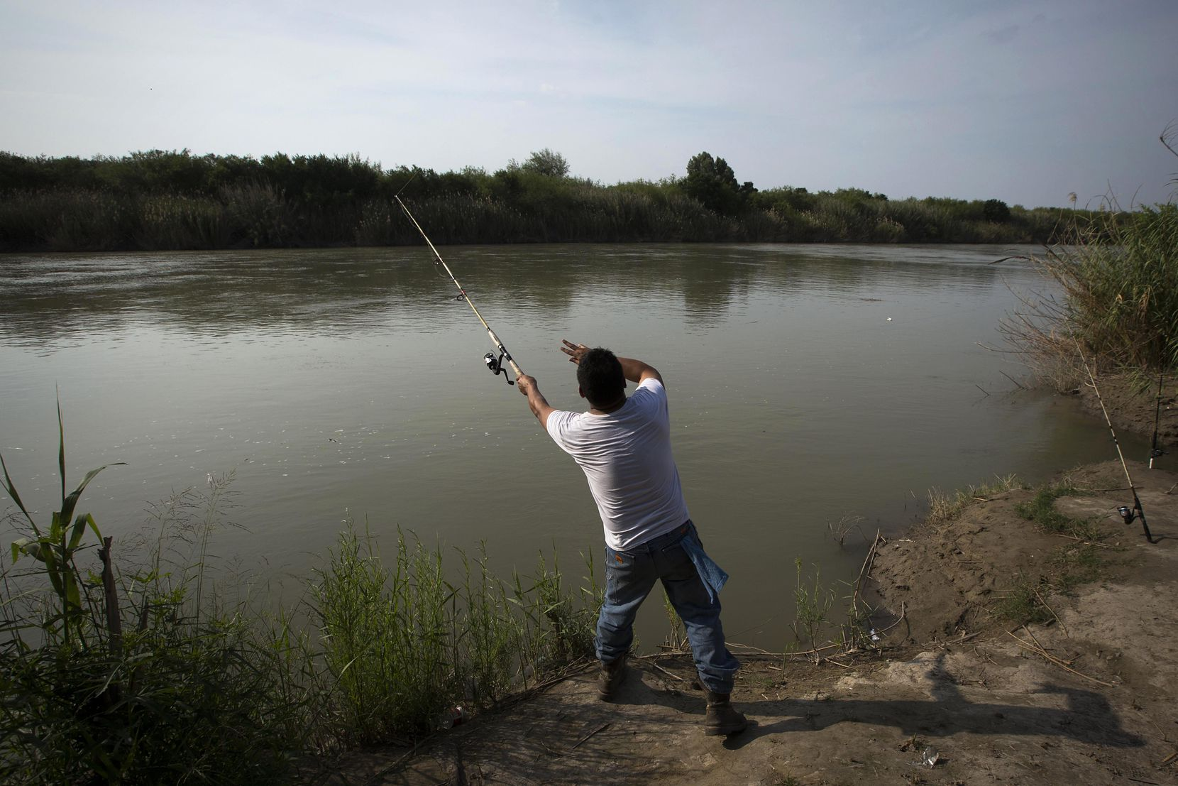 """Leo Ayala of Laredo, Texas, casts a line into the Rio Grande River while fishing on May 10, 2017, in El Cenizo, Texas, a small town with a """"safe haven"""" ordinance."""