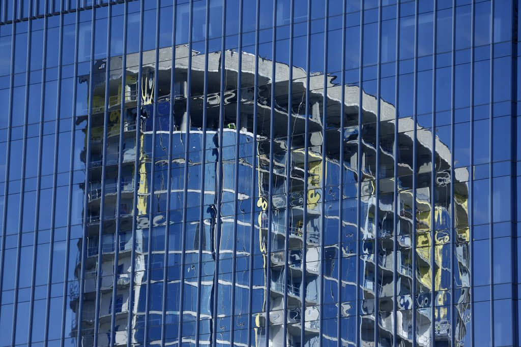 A luxury apartment tower under construction in the Legacy West area of Plano is reflected off another nearby building.