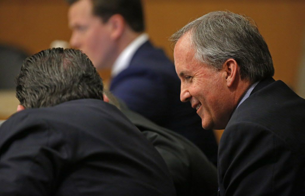 Texas Attorney General Ken Paxton (right) smiles during his pretrial hearing at Collin County Courthouse in McKinney, Texas, Thursday, Feb. 16, 2017.
