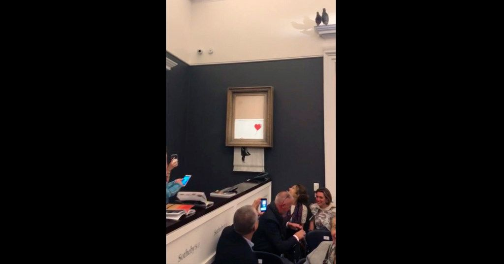 In this grab taken from video on Friday, people watch as the spray-painted canvas Girl With Balloon by artist Banksy is shredded at Sotheby's, in London.