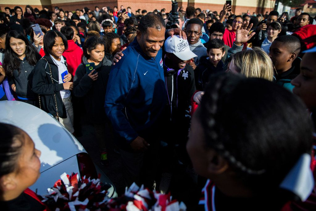 Coach Kevin MaBone greets students as he is surprised with a car during a presentation by students and teachers on Friday outside Wilkinson Middle School in Mesquite. (Ashley Landis/The Dallas Morning News)