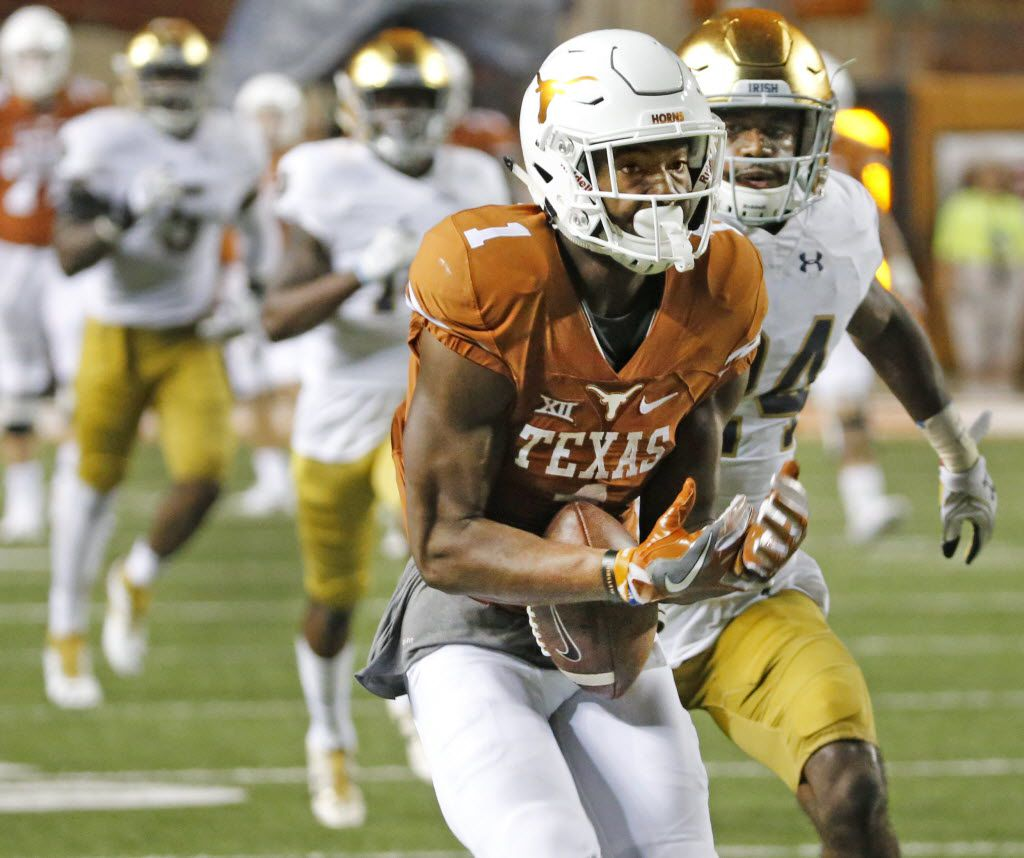 Texas wide receiver John Burt (1) barley hangs on to a long pass but is able to hold on to it and motor for a touchdown in the third quarter during the Notre Dame Fighting Irish vs. the University of Texas Longhorns NCAA football game at Darrell K. Royal Memorial Stadium in Austin on Sunday, September 4, 2016. (Louis DeLuca/The Dallas Morning News)