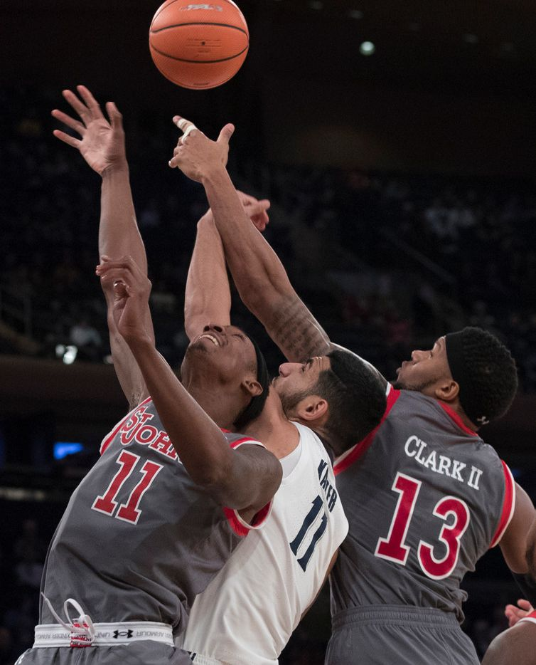 St. John's forwards Tariq Owens (11) and Marvin Clark II (13) battle for the ball with Xavier forward Kerem Kanter (11) during the first half of an NCAA college basketball game in the quarterfinals of the Big East conference tournament, Thursday, March 8, 2018, at Madison Square Garden in New York. (AP Photo/Mary Altaffer)