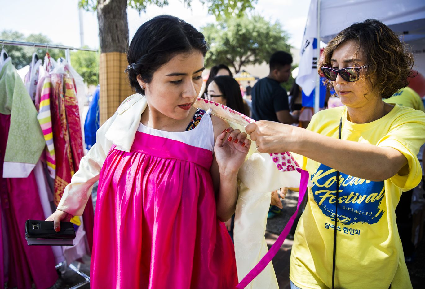 Mayra Herrera, left, tries on traditional Korean clothing with help from Myong Pak of The Korean Society of Dallas during the 27th Home Depot Asian Festival on Saturday, May 13, 2017 at Cotton Bowl Plaza in Dallas Fair Park.