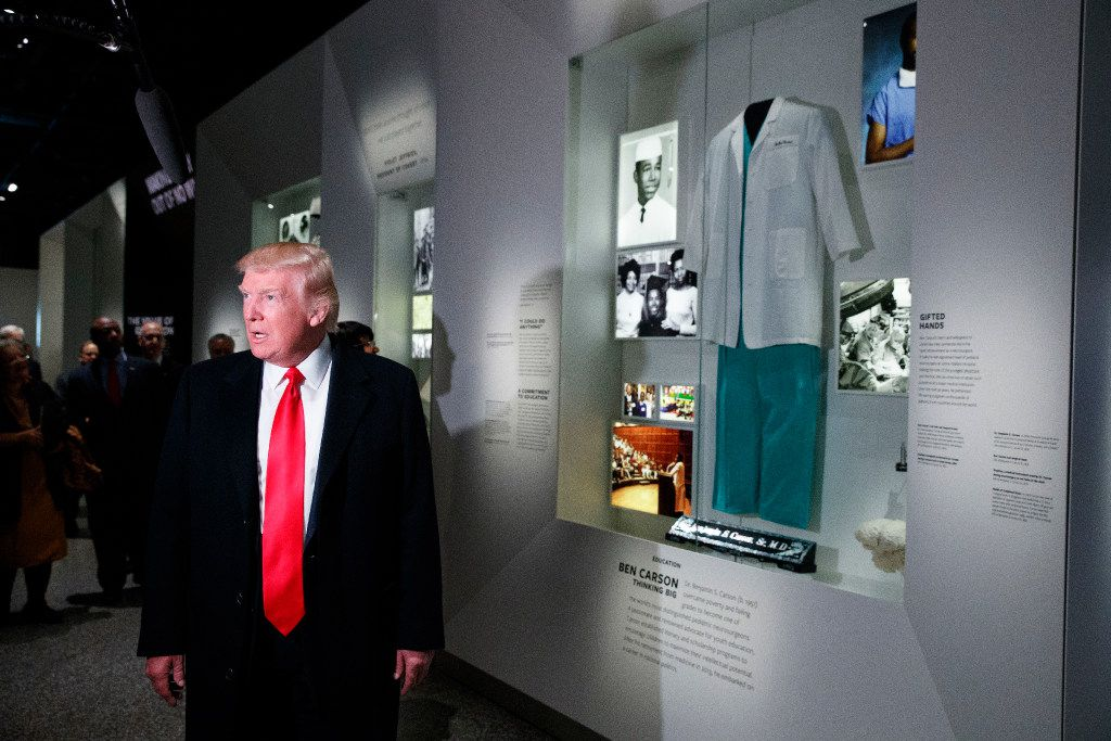 President Donald Trump talks with reporters as he stops at the exhibit for Dr. Ben Carson, his nominee for Housing and Urban Development secretary, during a tour of the National Museum of African American History and Culture, Tuesday, Feb. 21, 2017, in Washington. (AP Photo/Evan Vucci)