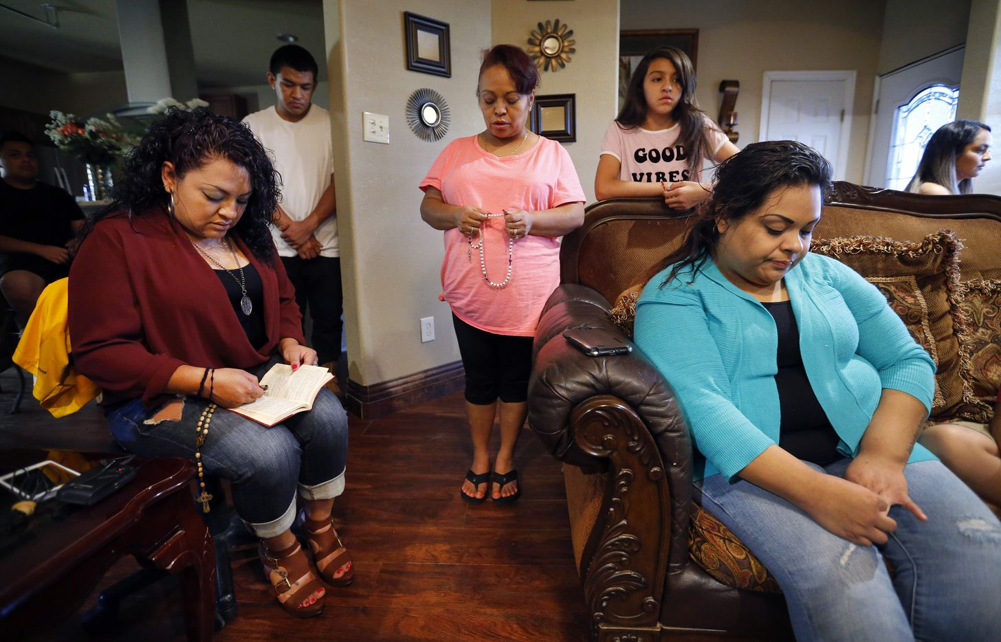 Ruddy Elizondo's aunt, Margarita Cardenas (left), leads the Rosary prayer at the family home in Garland, Friday, July 1, 2016. Ruddy's mother Alicia Elizondo (center) and cousin Elizabeth Cardenas (seated on couch) joined other family members in remembering him. Ruddy, a young man who was killed by a Garland police officer, is part of the increasing number of Texans who have been killed during arrests over the last 10 years statewide.