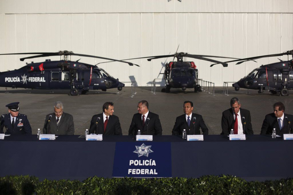 Mexico's Secretary of Public Safety Genaro Garcia Luna, center, speaks with U.S. Ambassador to Mexico Carlos Pascual, third right, during the delivery ceremony of three U.S. made helicopters to the Mexican government in Mexico City on Nov. 24, 2010.