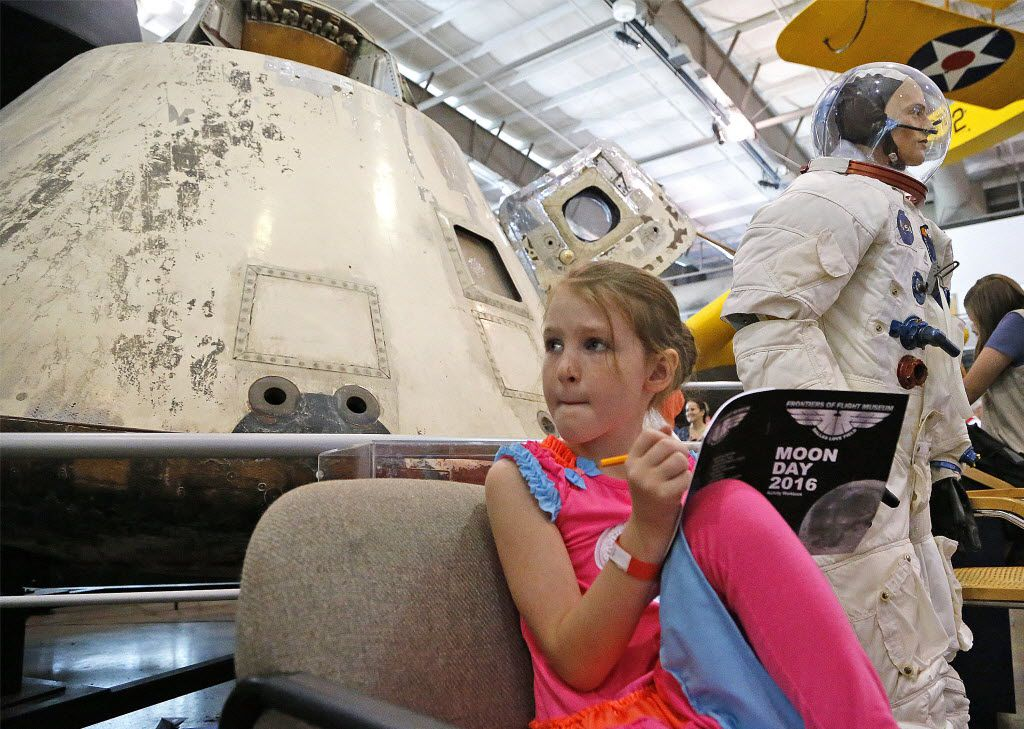 Macy Cleveland, then 7, of Royce City, filled out a Moon Day work book in front of the Apollo 7 capsule during a Moon Day event at the Frontiers of Flight Museum in Dallas in 2016.