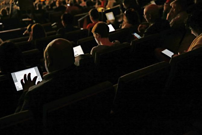 New Cities Summit participants work on their tablets and smartphones during a session at the Winspear Opera House in Dallas. The double-edged nature of technology was a constant theme on Wednesday, Day 2 of the three-day summit.