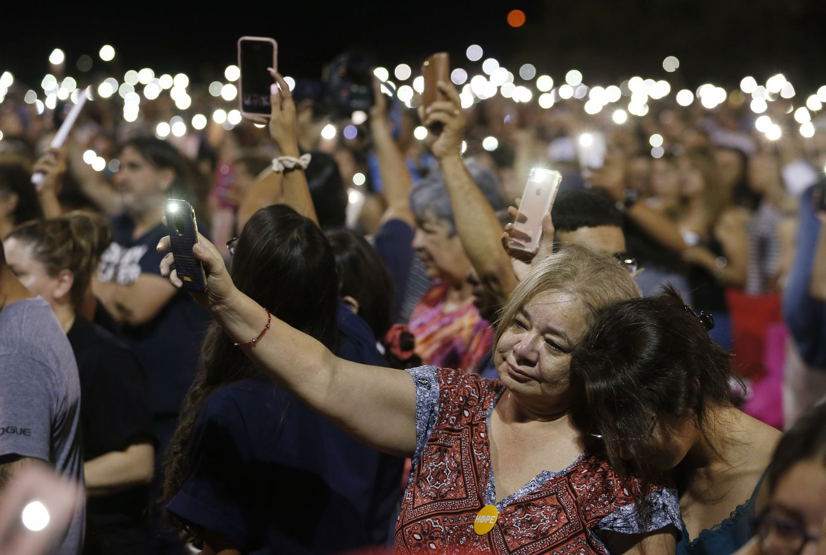 Martha Cortez (left) with her daughter Alexandra Cortez  both of El Paso join with the community during a vigil at Ponder park in El Paso, Texas on Sunday, August 4, 2019. Less than a mile away is the scene where 20 people were shot and killed and 26 more were wounded at a Walmart in El Paso on Saturday.
