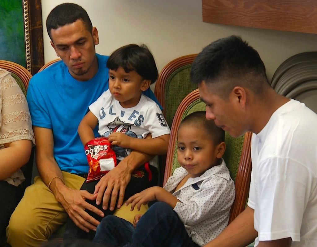 In this image taken from video, Javier Garrido Martinez (left) and Alan Garcia (right) sit with their 4-year-sons at a news conference in New York, on Wednesday, July 11. They men were reunited with their children after almost two months of separation.
