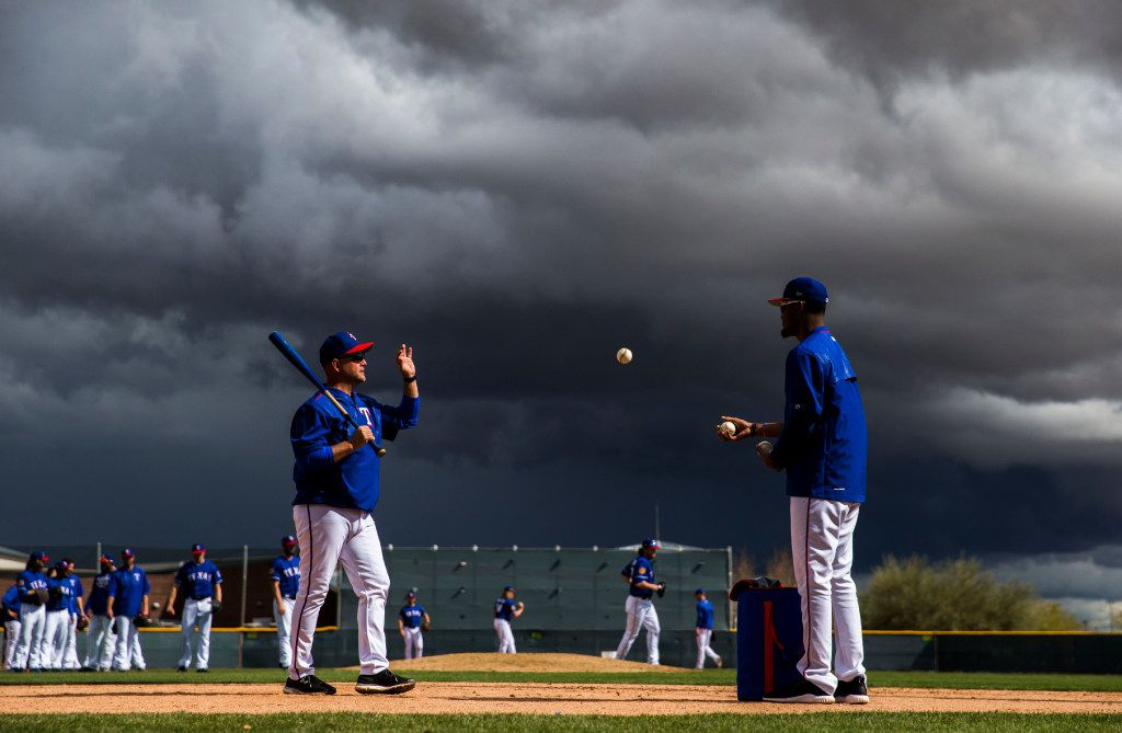 Texas Rangers relief pitcher Yohander Mendez (65) tosses a ball to minor league coach Danny Clark as rain clouds move in during a spring training workout at the teams' training facility on Tuesday, February 28, 2017 in Surprise, Arizona. (Ashley Landis/The Dallas Morning News)